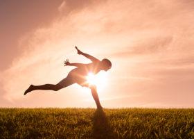 Person hoppar utomhus i siluett mot solen