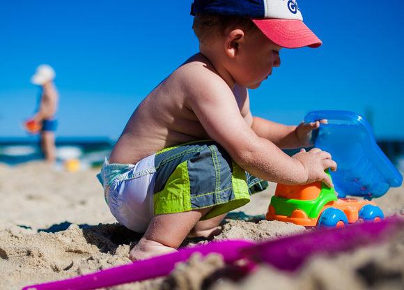 litet barn leker på stranden