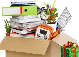 Kollage använda prylar i flyttkartong intill julklapp