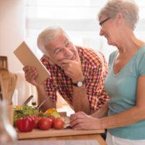 Leende äldre par i köket bland grönsaker