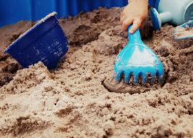 barn leker med plastleksak på strand