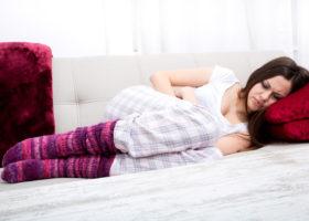 Tonårig mörkhårig flicka ligger på säng och håller sig om magen
