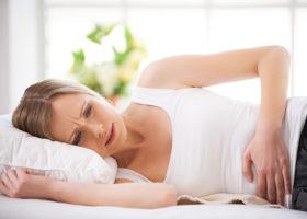 Grimaserande kvinna ligger och håller sig om magen
