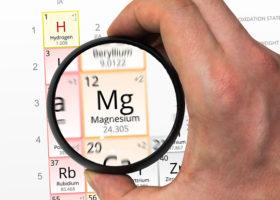 Hand håller förstoringsglas över kemisk benämning för magnesium