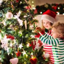 julgran som pyntas av två små barn