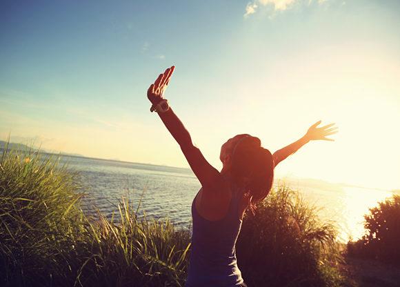 Kvinna utomhus vid havet med händerna upp i luften