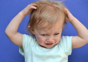 Litet barn kliar sitt huvud