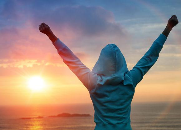 Kvinna håller upp händerna i luften i segerpose intill vatten och solnedgång