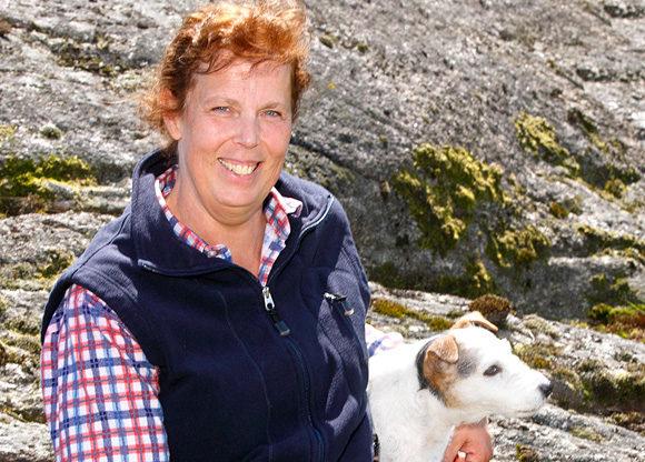 En glad Marie-Ann på en klippa med sin hund