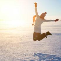 tjej hoppar högt i luften i vintermiljö