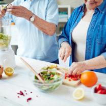 man och kvinna lagar grönsaker och smoothie i kök