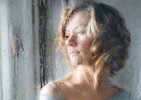 kvinna ser ut genom fönster