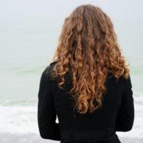 kvinna med lockigt hår vid havet