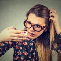 tjej tittar på sitt hår i kameraspegeln