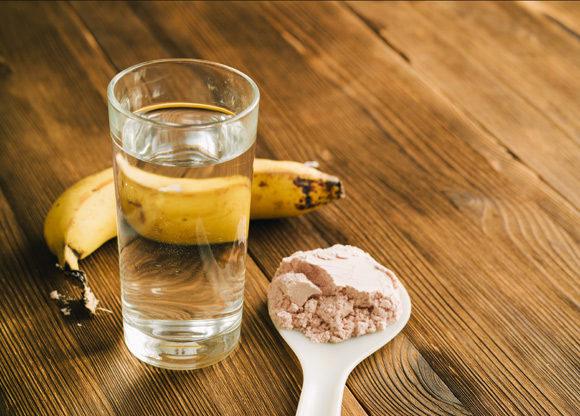 Beige proteinpulver, glas vatten och banan