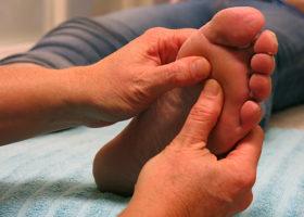 Händer utför zonterapi på fot