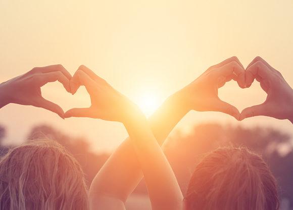 Två hjärtan formas av fyra par händer mot solnedgångsbakgrund