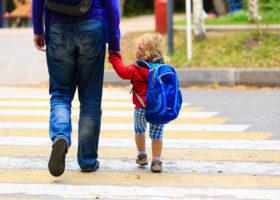 treårig flicka håller sin pappa i handen över övergångsställe