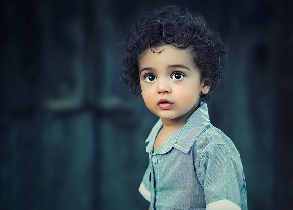 Liten brunögd pojke med lockigt hår