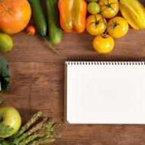 Grönsaker intill ett anteckningsblock och penna