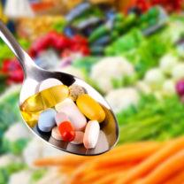 Kosttillskott på sked framför grönsaksdisk