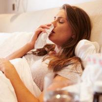 Sjuk tjej i sängen snyter sig