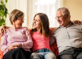 tonårig tjej mellan sina morföräldrar på soffan