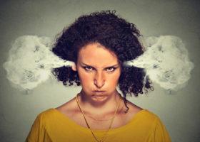 Kvinna med förgrymmad blick och rök som kommer ut ur öronen