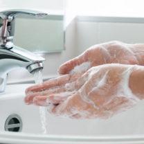 händer tvättas under kran