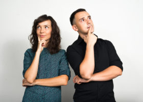 En kvinna och en man står med hakan i händerna och funderar