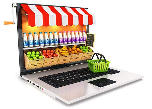 dator som förvandlats till fruktkiosk med varukorg ståendes på tangentbordet