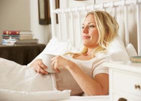 Småleende avslappnad blond kvinna i sängen med en tekopp