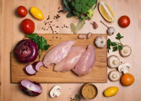 Färsk kyckling på träskärbräda intill andra råvaror
