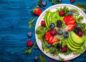 tallrik med avokado, jordgubbar, blåbär, sallad på blått träbord
