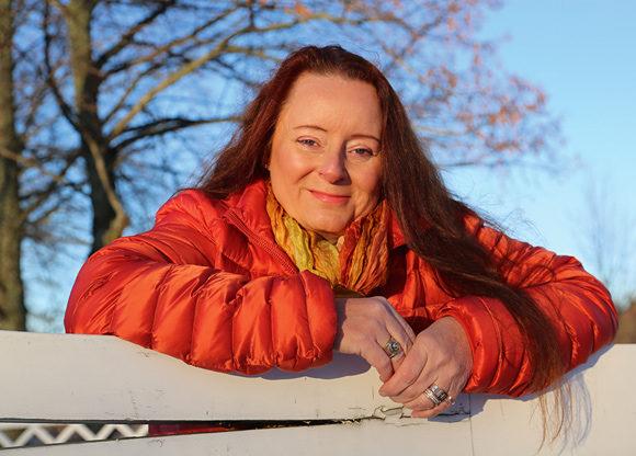 Pia Eriksson utomhus med blå himmel i bakgrunden
