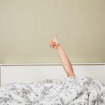 Ensam person sträcker upp handen ur täcke och gör tummen upp