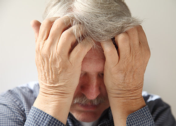 Till synes deppig medelålders man med huvudet i hälnderna