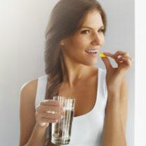 kvinna äter vitamintablett