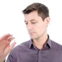 man i 30-årsåldern tittar på ett piller som han håller i sin hand