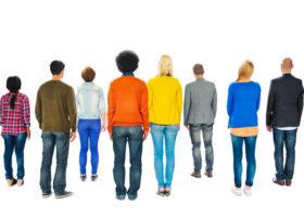 åtta personer vända från kameran mot vit bakgrund