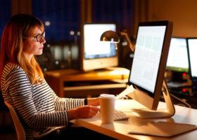 Kvinna jobbar sent vid sin dator