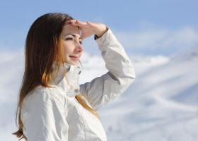 ung kvinna i vinterjacka utomhus i solsken