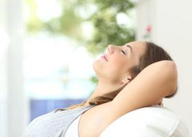 Leende tillbakalutad kvinna med synliga nakna armhålor