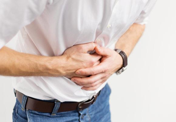 man håller sina händer för magen som om smärta