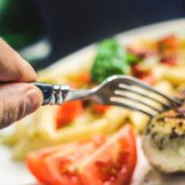 hand, gaffel och tallrik med kyckling och grönsaker