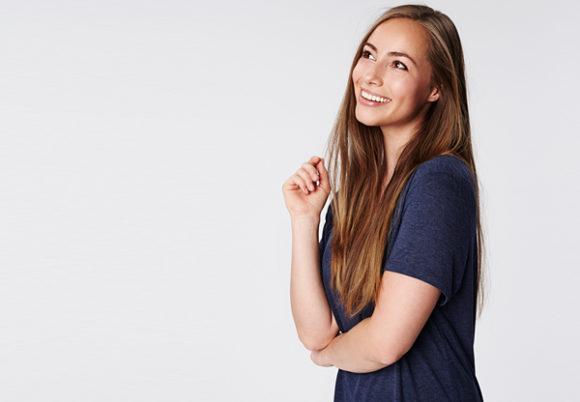 flicka med vacker hy och långt hår håller arm vid magen
