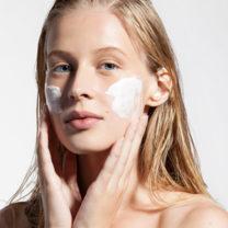 Osminkad naturligt vacker kvinna med fläckar av hudkräm på kinderna