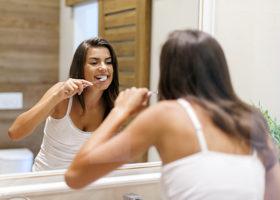 Kvinna borstar tänderna med en bra tandkräm