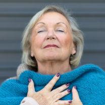 Kvinna håller sig för bröstet med lättad min