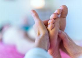 hand trycker på punkter på patients fot